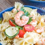 cold shrimp pasta salad has all the good stuff - bowtie pasta, grape tomatoes, zucchini, and shrimp all tossed in a yummy pesto vinaigrette